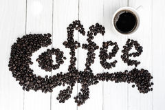 Fond de café avec les haricots et la tasse blanche Copiez l'espace Image stock