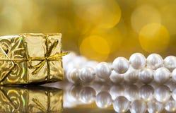 Fond de carte de Noël - boîte-cadeau d'or avec des perles photos stock