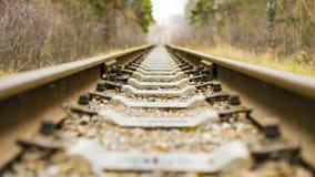 Fond de chemin de fer diagonal au crépuscule avec l'espace de copie Rails, dormeurs, attaches et fin en pierre écrasée  Chemin de photos stock