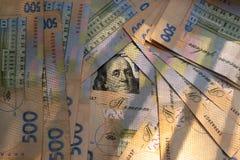 Fond de cinq cents billets de banque ukrainiens de hryvnia et de billet de banque simple de cent dollars photos libres de droits
