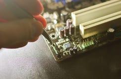 Fond de composants électroniques de Smd La main avec des brucelles tient la résistance sur une puce photos libres de droits