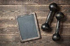 Fond de concept de séance d'entraînement avec les haltères de fer et le panneau de craie Images stock