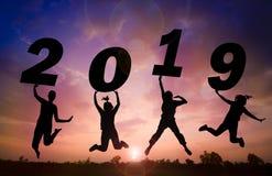 Fond de coucher du soleil de silhouette et nouvelle année Ils sautent dedans au mot de ciel et d'ascenseur 2019 photographie stock