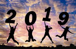 Fond de coucher du soleil de silhouette et nouvelle année Ils sautent dedans au mot de ciel et d'ascenseur 2019 photo stock