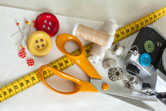Fond de couture avec des fils, des boutons, le mètre et des ciseaux de couleur Images stock