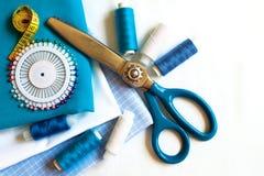 Fond de couture avec les fils, le mètre, les goupilles et les ciseaux de couleur Image stock