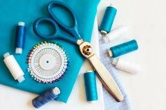 Fond de couture avec les fils, le mètre, les goupilles et les ciseaux de couleur Images stock