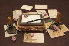 Fond de cru avec des livres, des cartes postales et la photo Photographie stock