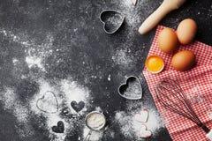 Fond de cuisson avec de la farine, la goupille, les oeufs, et la forme de coeur sur la vue supérieure foncée de table de cuisine  Photos stock