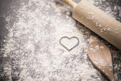 Fond de cuisson avec la forme de coeur dans la farine Photo stock