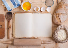 Fond de cuisson avec le livre vide de cuisinier, coquille d'oeuf, farine, roulement Photographie stock