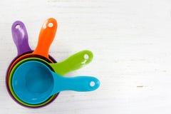 Fond de cuisson avec les tasses de mesure colorées lumineuses sur W rustique Images libres de droits