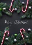 Fond de décoration de Noël ou de nouvelle année Branches d'arbre de sapin, sucrerie, boules colorées sur le fond noir avec l'espa Photo libre de droits