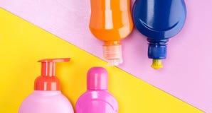 Fond de deux couleurs, jaune et rose avec un ensemble de bouteilles pour les liquides de nettoyage photo stock