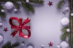 Fond de fête avec le boîte-cadeau argenté avec le ruban rouge sur le papier gris entouré par les étoiles de branches de sapin, ro photo stock