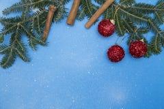 Fond de fête bleu avec les branches, les boules et la cannelle impeccables Images stock