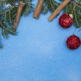 Fond de fête bleu avec les branches, les boules et la cannelle impeccables Photographie stock libre de droits