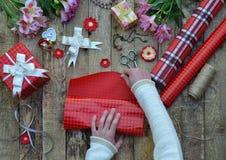 Fond de fête La composition de vue supérieure des mains de femme enveloppent le présent pour l'anniversaire, jour du ` s de mère, Photo libre de droits