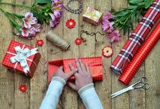 Fond de fête La composition de vue supérieure des mains de femme enveloppent le présent pour l'anniversaire, jour du ` s de mère, Photo stock