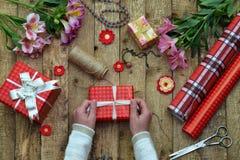 Fond de fête La composition de vue supérieure des mains de femme enveloppent le présent pour l'anniversaire, jour du ` s de mère, Photos stock