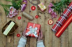 Fond de fête La composition de vue supérieure des mains de femme enveloppent le présent pour l'anniversaire, jour du ` s de mère, Photographie stock libre de droits