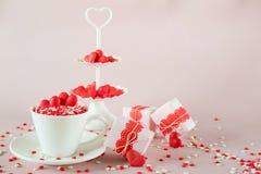Fond de fête La tasse de café, le plateau à deux niveaux blanc de portion complètement du bonbon multicolore arrose les coeurs de Photo libre de droits
