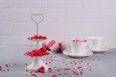 Fond de fête La tasse de café, le plateau à deux niveaux blanc de portion complètement du bonbon multicolore arrose les coeurs et Photographie stock