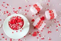 Fond de fête La tasse de café, pleine du bonbon multicolore arrose des coeurs de sucrerie de sucre et des cadeaux de emballage de Photos libres de droits