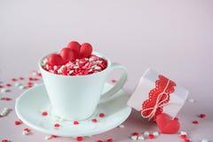 Fond de fête La tasse de café, pleine du bonbon multicolore arrose les coeurs de sucrerie de sucre et le cadeau de emballage de j Image libre de droits