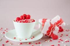 Fond de fête La tasse de café, pleine du bonbon multicolore arrose les coeurs de sucrerie de sucre et le cadeau de emballage de j Photos libres de droits