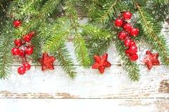 Fond de fête de Noël Branches de sapin avec les baies et les étoiles rouges sur le fond en bois blanc images libres de droits