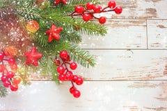 Fond de fête de Noël Branches de sapin avec les baies et les étoiles rouges sur le fond en bois blanc image libre de droits
