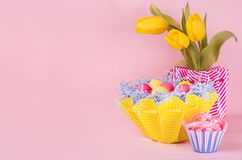 Fond de fête de Pâques - jaune, oeufs bleus et rouges dans le panier jaune, tulipes, petit gâteau sur le fond de rose en pastel a photographie stock
