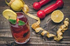 Fond de forme physique avec des haltères, centimètre, cocktail, citron Photographie stock
