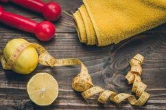 Fond de forme physique avec des haltères, centimètre, serviette, citron Image stock