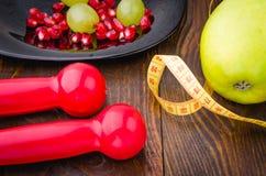 Fond de forme physique avec les haltères, la grenade, les raisins, la pomme et le centimètre Photos libres de droits