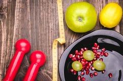 Fond de forme physique avec les haltères, le citron, les raisins, la pomme, la grenade et le centimètre Image stock