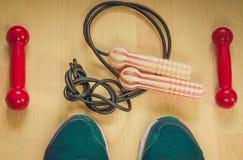 Fond de forme physique avec les haltères rouges, la corde à sauter et les chaussures sportives Vue de ci-avant Images stock