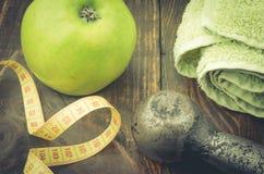 Fond de forme physique de centimètre, de pomme une serviette et d'haltère Photographie stock