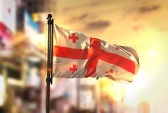Fond de Georgia Flag Against City Blurred au lever de soleil Backligh Photo libre de droits