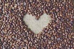 Fond de grains de café avec le cadre de coeur de toile de jute Photographie stock libre de droits