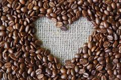 Fond de grains de café avec le cadre de coeur de toile de jute Photos stock