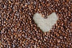 Fond de grains de café avec le cadre de coeur de toile de jute Photo stock