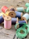 Fond de hippie de vintage de vieille table en bois de bobines multicolores de fils Atelier, contexte de couture d'accessoires Photo libre de droits
