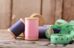 Fond de hippie de vintage de vieille table en bois de bobines multicolores de fils Atelier, contexte de couture d'accessoires Image libre de droits