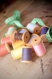 Fond de hippie de vintage de vieille table en bois de bobines multicolores de fils Atelier, contexte de couture d'accessoires Images stock