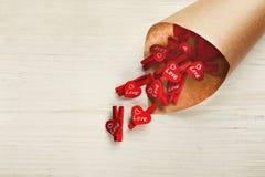 Fond de jour d'amants avec les pinces à linge rouges dans le cornet de métier Image libre de droits