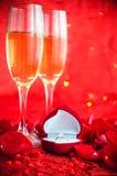Fond de jour de valentines avec le champagne, l'anneau et les pétales de rose Image stock