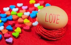 Fond de jour de valentines avec le texte d'amour sur l'oeuf et le hea coloré Image stock