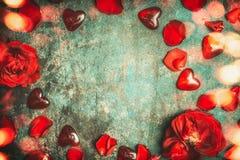 Fond de jour de valentines avec les roses rouges, les pétales, le coeur en verre et l'éclairage de bokeh, vue supérieure Image stock